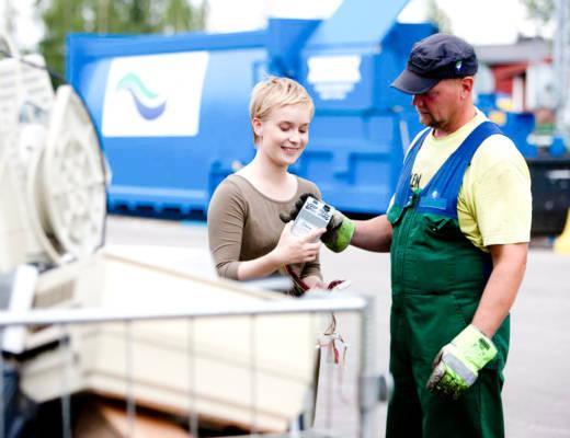 Jäteasemanhoitaja opastaa asiakasta.
