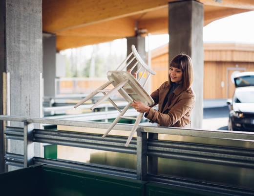 Nainen lajittelee rikkinäisen tuolin jäteasemalla.