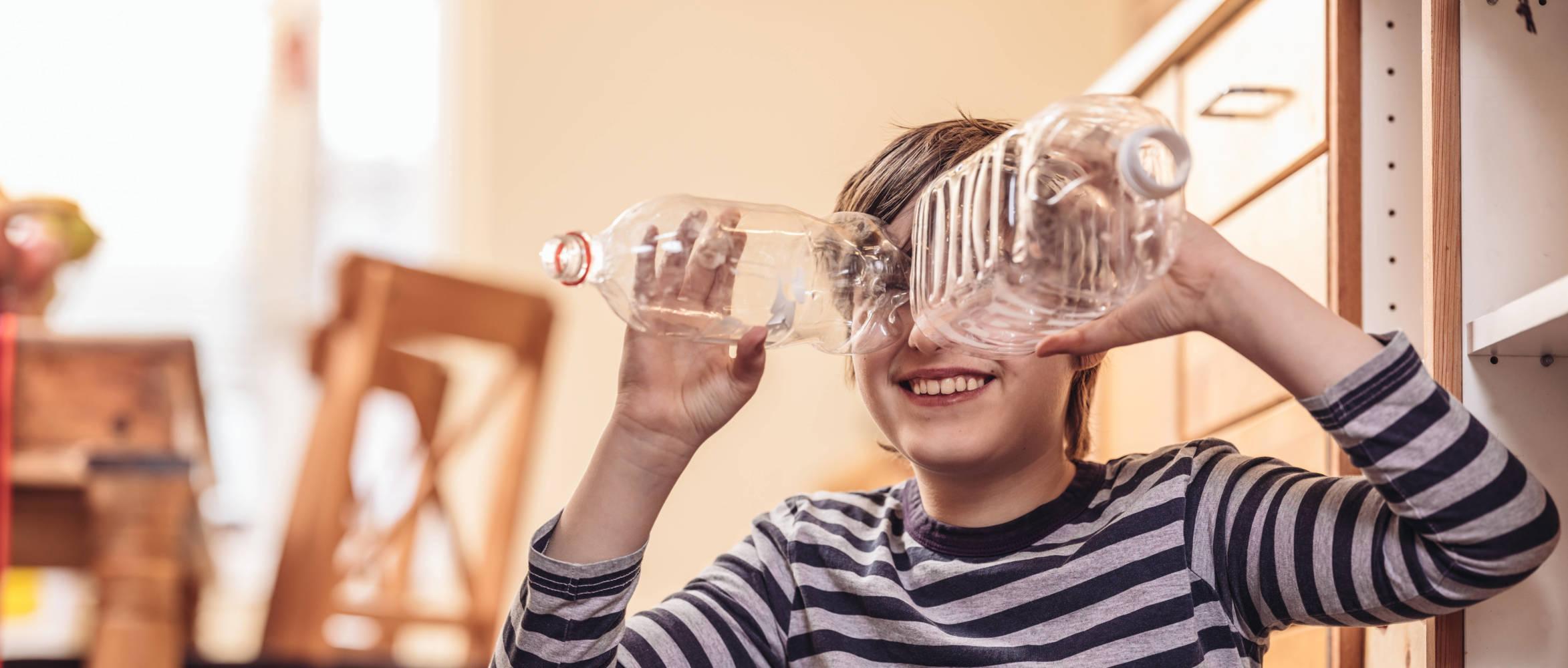 Poika ja muoviset pullot