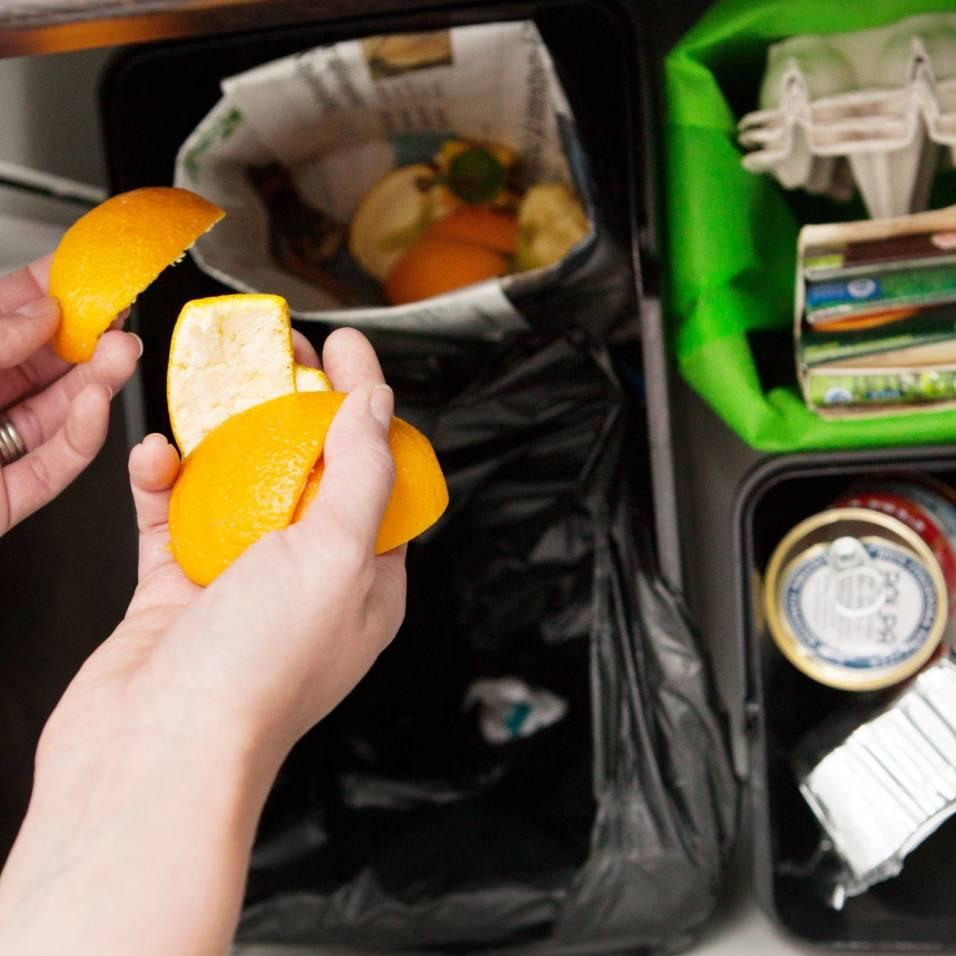 Kädet laittavat appelsiininkuoria biojäteroskikseen.
