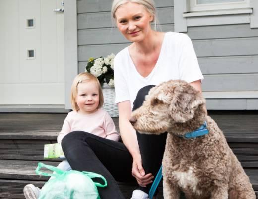 Nainen, lapsi ja koira istuvat talon rappusilla.