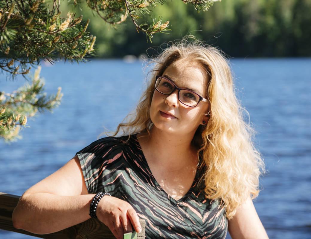 Paula istuu auringossa järven rannalla.
