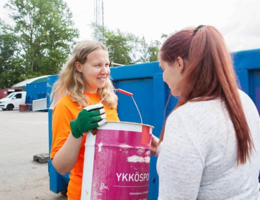 Nainen ojentaa hymyilevälle jäteasemanhoitajalle tyhjän maaliämpärin.