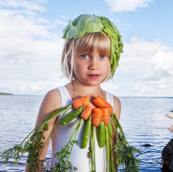 Vaalealla tytöllä on päällään biomuotia: kaalinlehti hattuna ja porkkanoita kaulakoruna.